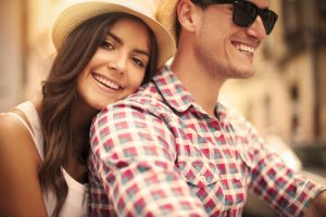 couple earing straw hats smiling
