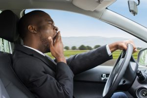 man yawning in car from sleep apnea