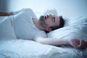 man sleeping on bed with mouth open